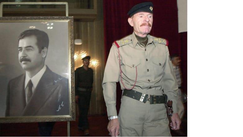 عزة إبراهيم الدوري في صورة التقطت بتاريخ 20 أغسطس/ آب 2001 وهو يمر بجانب صورة لصدام حسين لإلقاء كلمة في مؤتمر ببغداد
