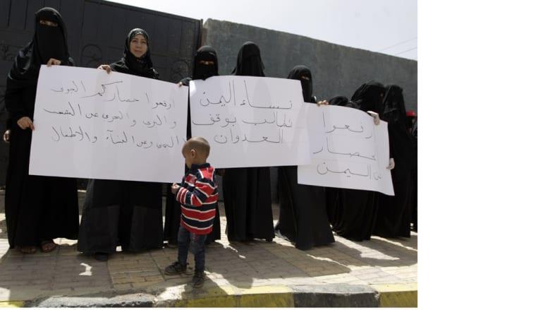 طفل يمني أمام سيدات يرفعن شعارات معارضة لعاصفة الحزم في صنعاء 15 أبريل/ نيسان 2015