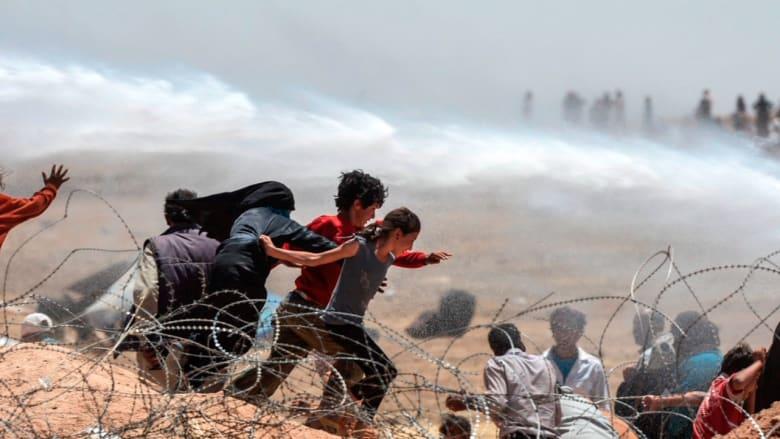 كيف اقتحم آلاف السوريين الحواجز الحدودية مع تركيا؟ وما سر ابتسامة عناصر داعش؟