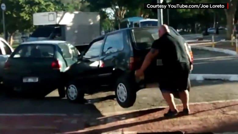 """بالفيديو.. """"هالك البرازيل"""" يرفع سيارة حتى يعبر بدراجته"""