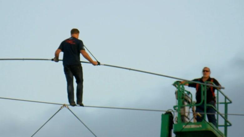 شاهد.. مغامر يسير فوق حبل على ارتفاع 10 طوابق لمسافة 1600 قدم
