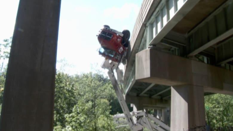 بالفيديو.. انقلاب شاحنة من جسر وتعلقها في الهواء