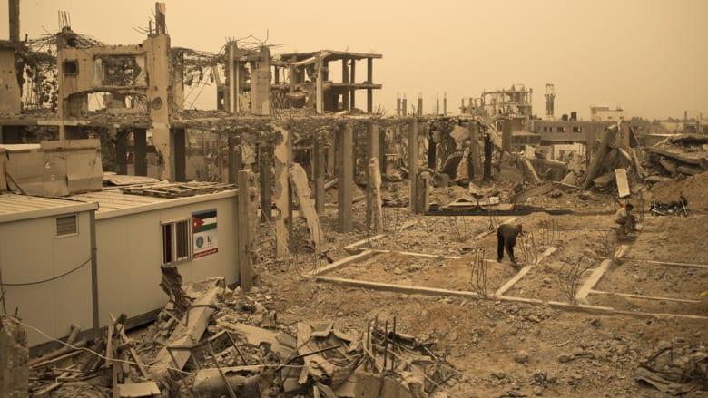 عمال فلسطينيون يزيلون الحطام من المباني التي دمرت خلال الحرب بين اسرائيل وحماس في صيف 2014