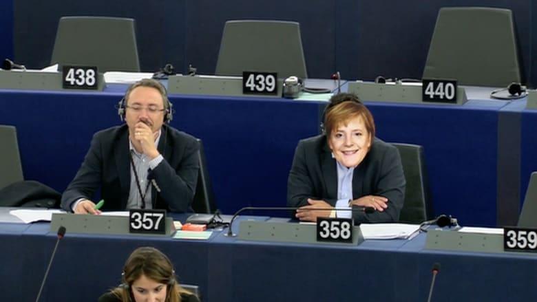 بالفيديو.. عضو بالمفوضية الأوروبية يضع قناعا لوجه ميركل خلال جلسة لمناقشة أزمة اللاجئين