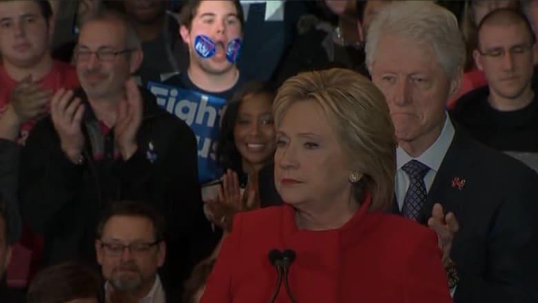 """بالفيديو: """"فتى الملصقات"""" يغير تعابير وجهه ويسرق أضواء الشهرة من هيلاري كلينتون"""