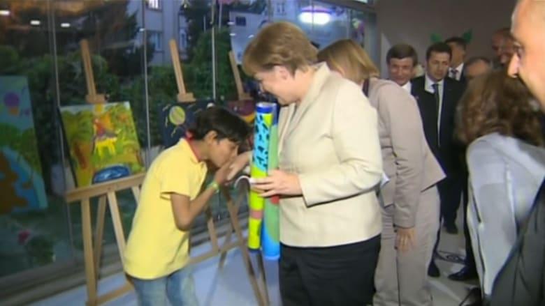 بالفيديو: طفل يقبل يد ميركل خلال زيارتها إلى مخيم للاجئين السوريين في تركيا