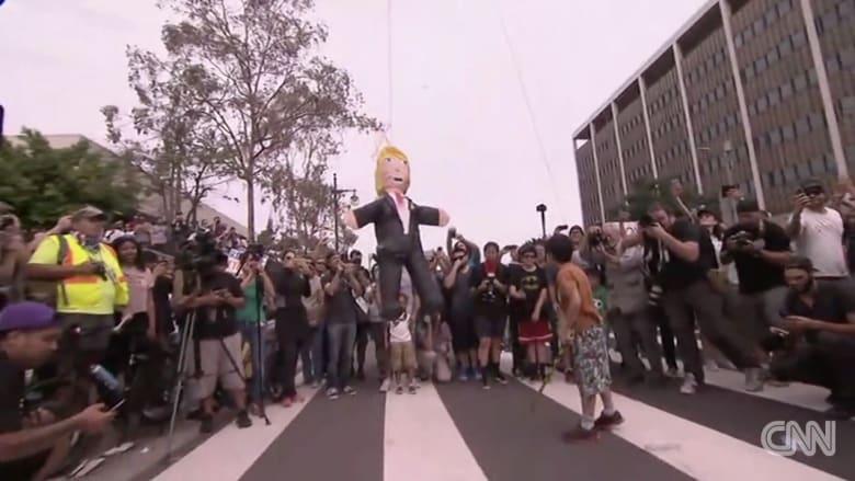 أطفال يضربون دمية لترامب خلال مظاهرة في لوس أنجلوس