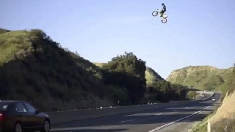 قفزة خطرة لدراجة نارية فوق السيارات على طريق سريع
