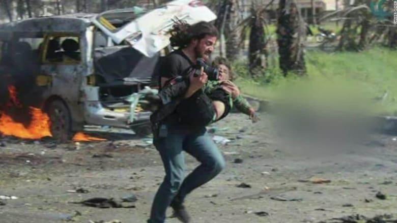 مصور سوري يحمل على يديه طفلاً أنقذه.. وكاميرا