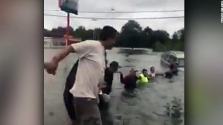 شاهد.. سلسلة بشرية لإنقاذ مسن من سيارة وسط الفيضانات