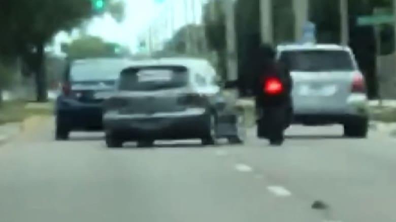 شاهد.. غضب سائق سيارة يدفعه للاصطدام براكب دراجة نارية