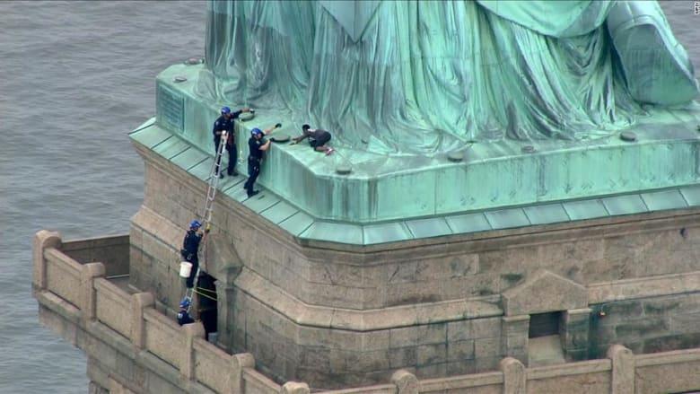 بذكرى الاستقلال.. شاهد امرأة تتسلق تمثال الحرية احتجاجاً