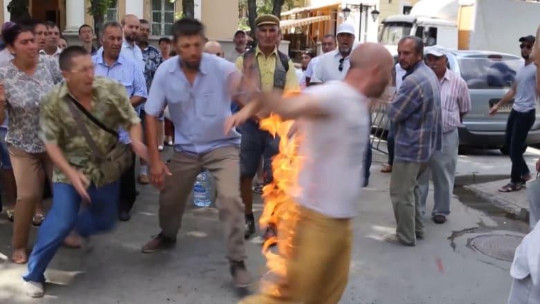 """شاهد.. ناشط من القرم يحتج بـ""""النار"""" على قانون بناء"""