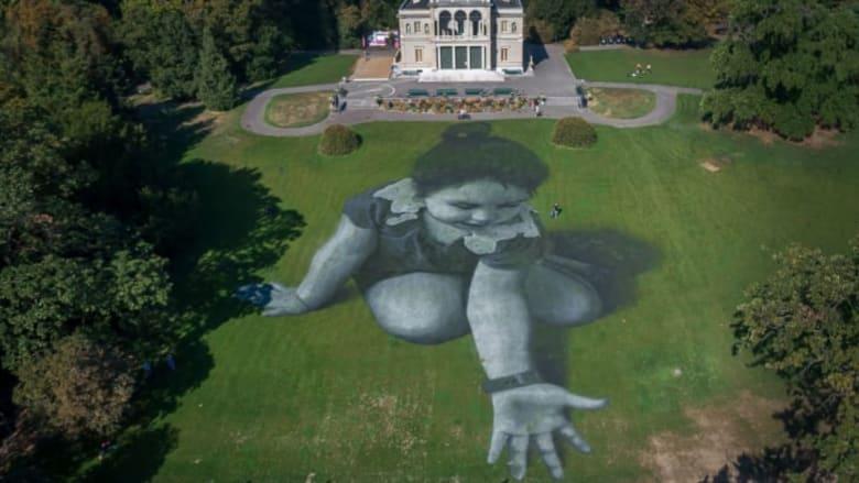 """بلوحة ضخمة على العشب.. فنان فرنسي يبتدع """"رسالة أمل"""" للاجئين"""