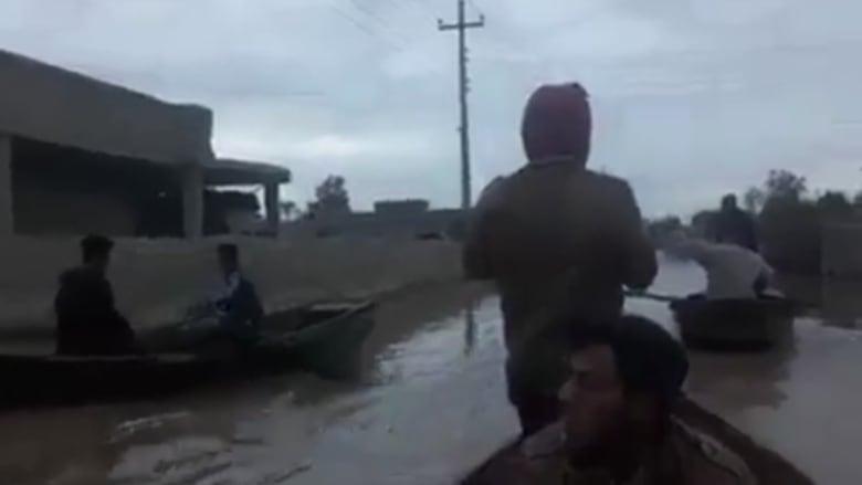 عراقيون يتجولون بالقوارب بين المنازل بحثاً عن ناجين