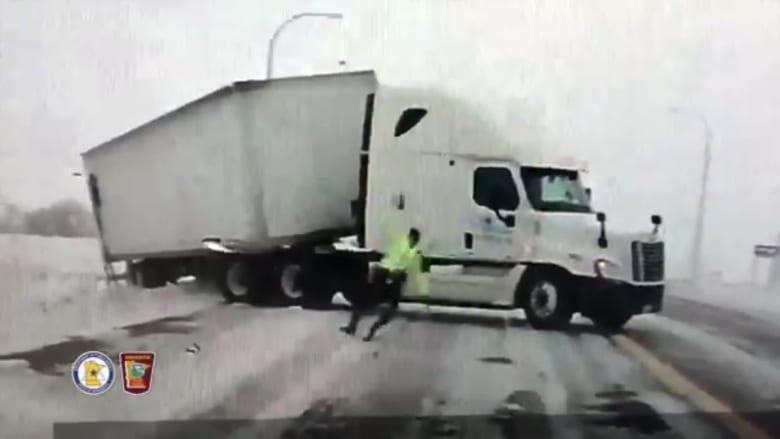 رياح قوية تدفع شرطيا أمريكيا وتسقطه أرضاً على طريق سريع