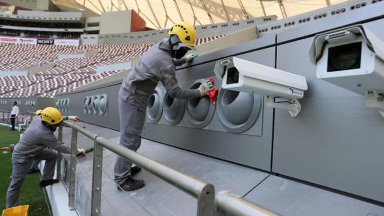 عمال ينظفون أنظمة التبريد في استاد خليفة الدولي في الدوحة