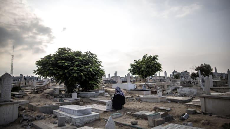 صورة ارشيفية لامرأة تجلس إلى جانب قبر