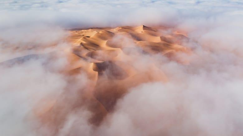 """كثبان رملية """"تنبثق"""" من الضباب ومشهد غير اعتيادي تشهده صحراء أبوظبي"""