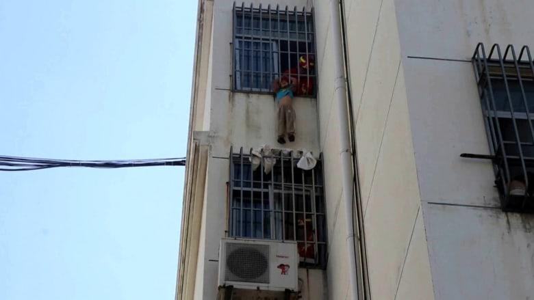 شاهد عملية إنقاذ طفل علق رأسه في سور نافذة بالطابق الخامس