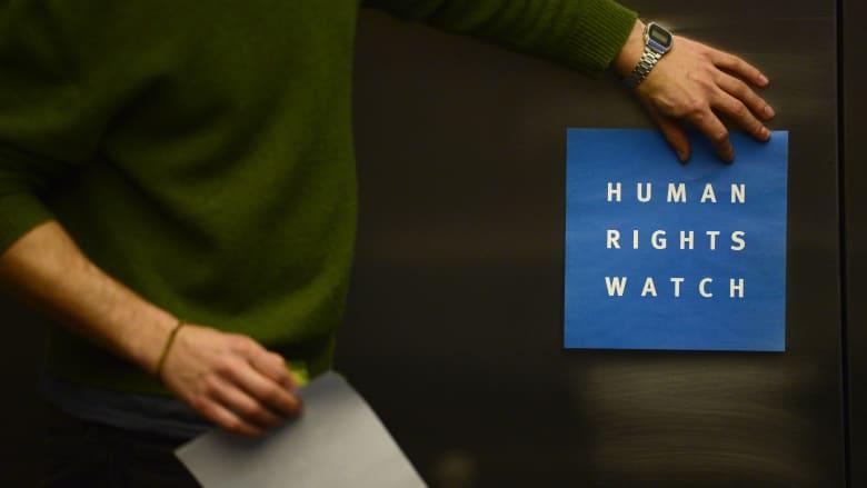 صورة ارشيفية لرجل يضع ملصقا لمنظمة هيومن رايتس ووتش