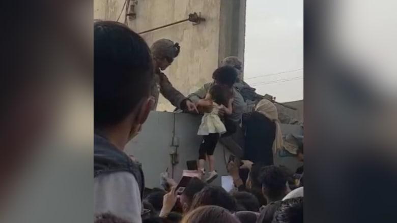 وسط اليأس.. أفغاني يسلم طفلة فوق الأسلاك الشائكة إلى جندي بمطار كابول