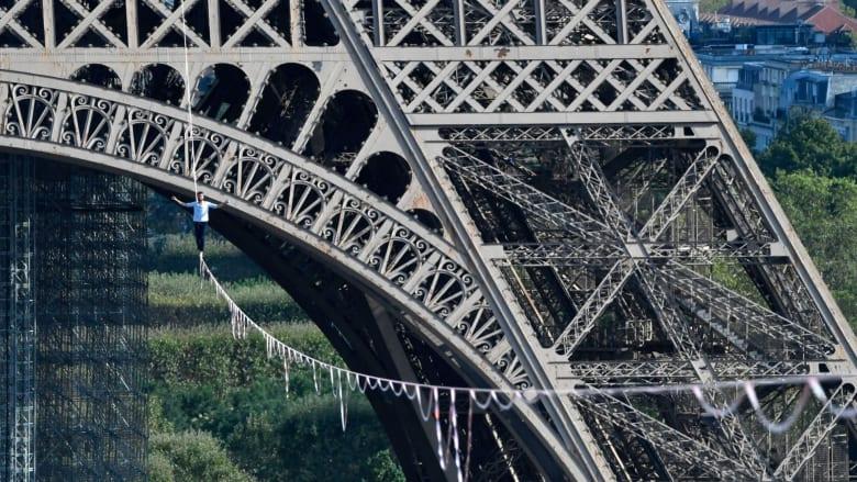 في مشهد يحبس الأنفاس.. مغامر فرنسي يسير على حبل معقود بين برج إيفل ونهر السين
