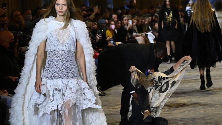 """ناشطات في مجال المناخ """"يقتحمن"""" عرض أزياء في باريس.. ورجل أمن بالمرصاد"""