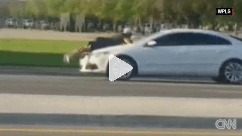 """حالة سيئة من """"غضب الطرقات"""".. رجل معلق بمقدمة سيارة والسائق لا يكترث"""