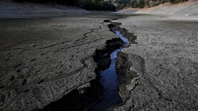 تيار مياه يسري بين شقوق الأرض الجافة
