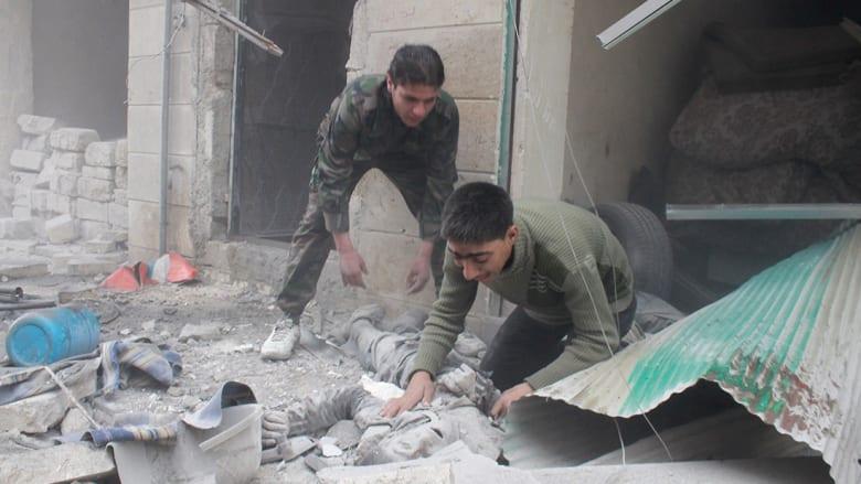 رجال سوريون بعد غارة جوية على حلب.
