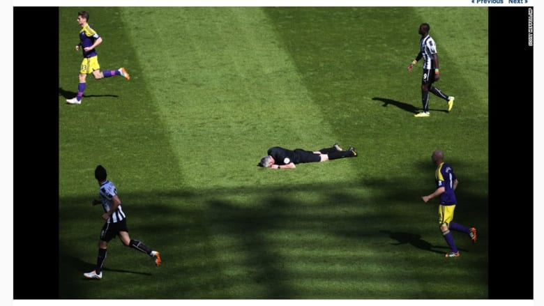 """الحكم """"كريس فوي"""" بعد أن أصيب بالكرة في وجهه خلال الدوري الانجليزي لكرة القدم نيوكاسل وسوانسي سيتي ."""