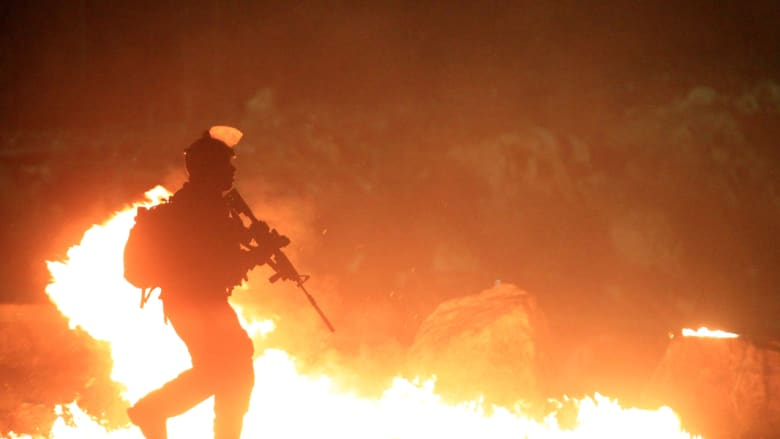 جندي إسرائيلي يجتاز إطارات أشعلها متظاهرون فلسطينيون في قلنديا