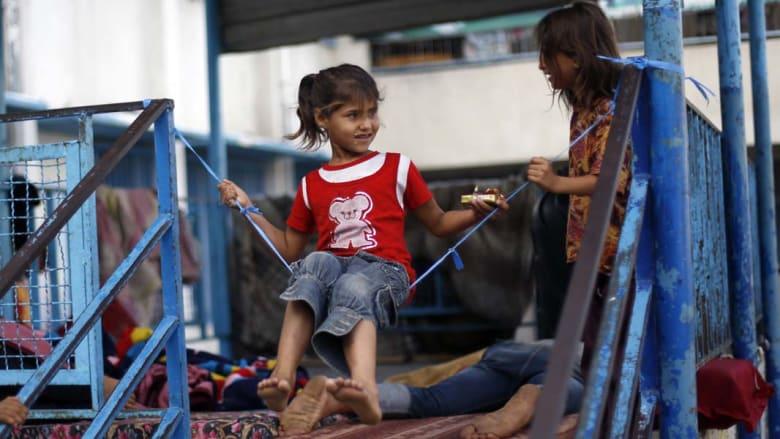 طفلة تصنع أرجوحتها في الملجأ