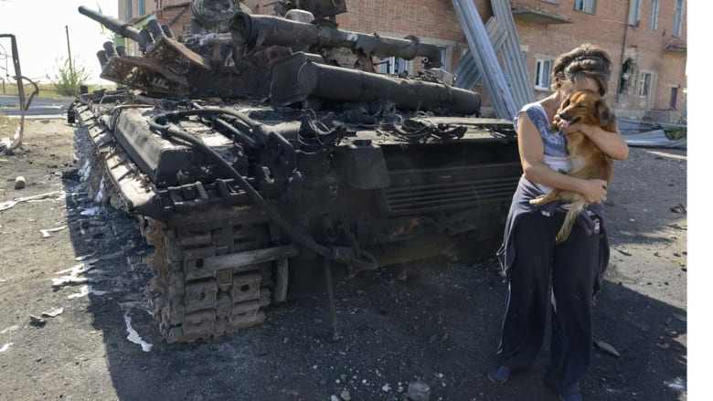 تلاكوفكا، أوكرانيا-- إمرأة تحمل كلبها أمام أحد الدبابات المدمرة في قرية تلاكوفكا شرق أوكرانيا، بعد يوم من توقيع الانفصاليين الموالين لروسيا على اتفاق لوقف إطلاق النار مدته خمسة أشهر 6 سبتمبر/ أيلول 2014