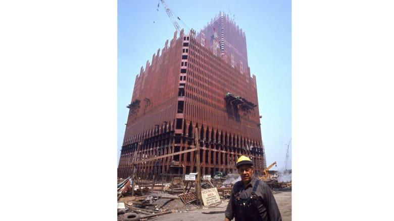 عامل بناء يسير بجانب مبنى مركز التجارة العالمي خلال مراحل الانشاء 1970