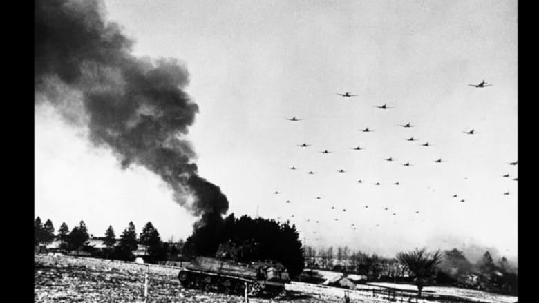 دبابة أمريكية تحترق، وتشاهد في الأفق طائرات نقل عسكرية تحلق في الأجواء أثناء المعارك