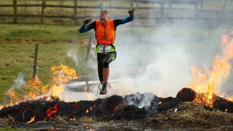 متنافس يقفز فوق أعشاب محترقة