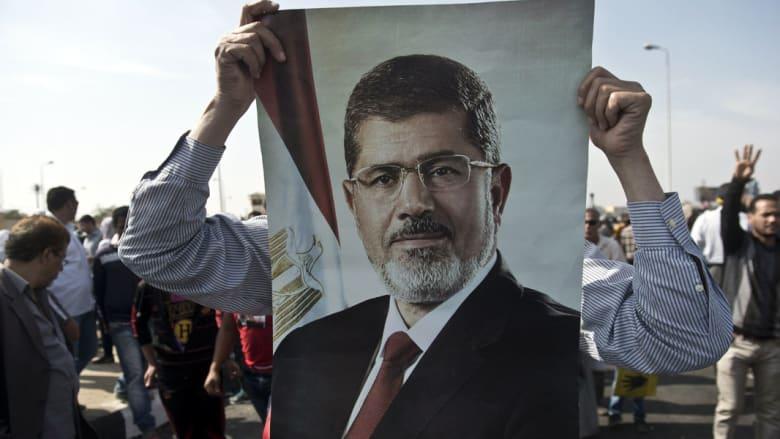 """مرسي يحيي الشعب بمحكمة """"وادي النظرون"""".. والمحكمة ترد: """"تاني.. مالكش دعوة بالشعب"""""""