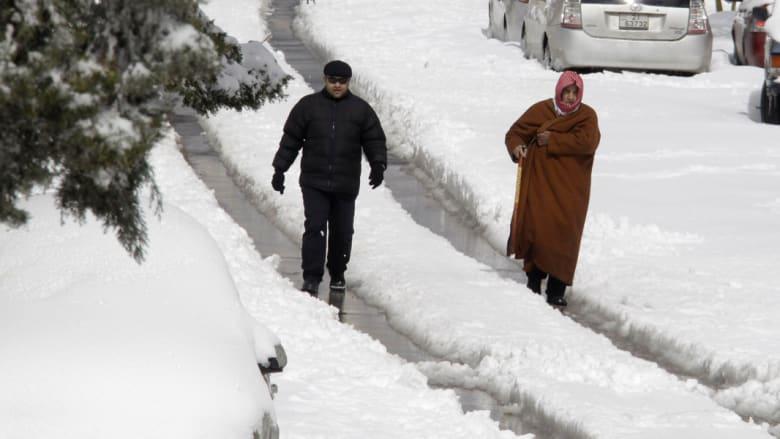 رجلان أردنيان يمشيان في شارع تغطيه الثلوج في عمان