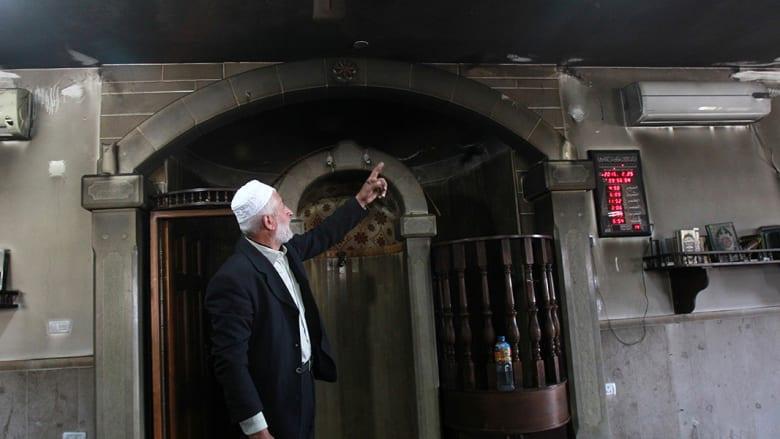إمام المسجد يشير إلى الآثار التي خلفها الحريق.