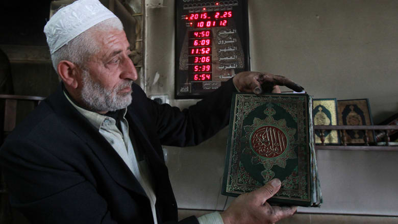 إمام المسجد يحمل القرآن الذي طالته ألسنة اللهب