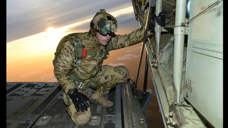 """جندي يتفقد الأوضاع قبيل بدء رفاقه القفز بالمظلات من طائرة النقل """"سي-130"""""""