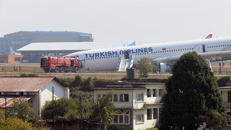 رجال الاطفاء وعمال الانقاذ بالقرب من الطائرة