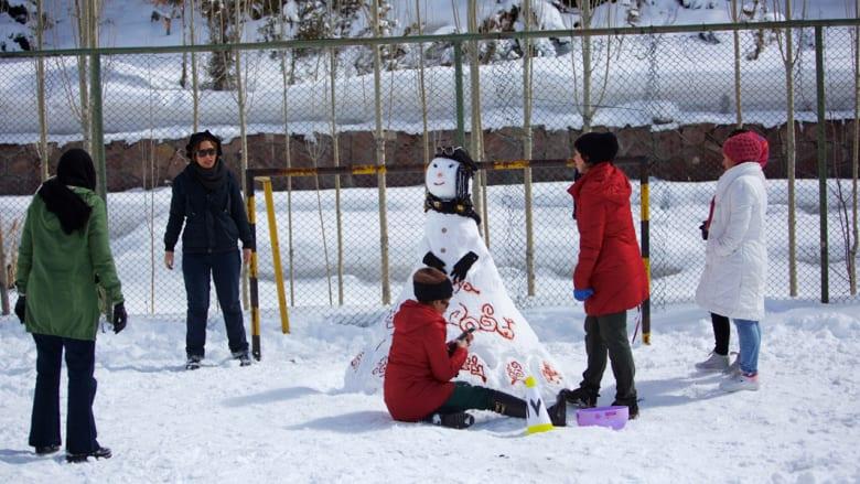 إيرانية تنظر بإعجاب لتشكيل ثلجي أعدته بمساعدة بقية أفراد الأسرة