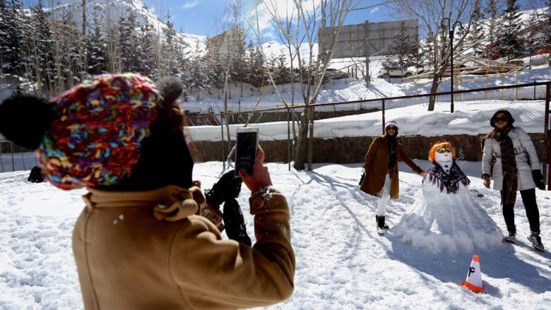يرانيتان تقفان قرب تشكيلتهما الثلجية أثناء التقاط صورة لهما