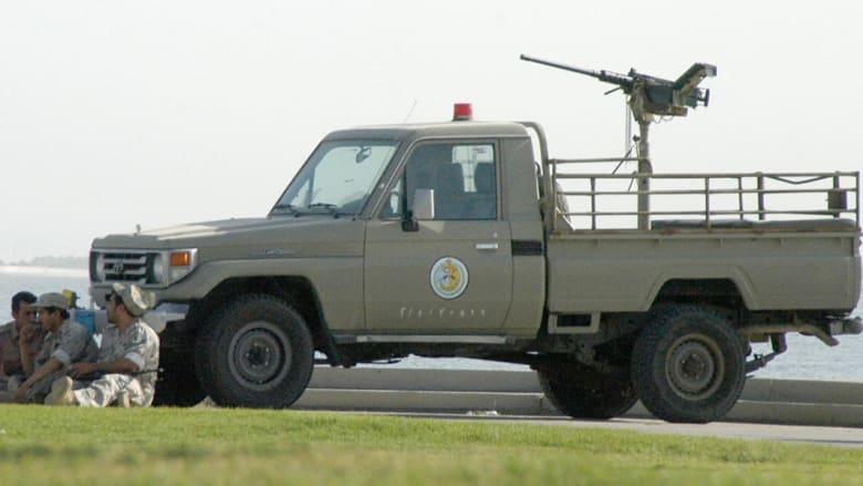 رجال أمن سعوديون يجلسون قرب سيارتهم المجهزة بالأسلحة.