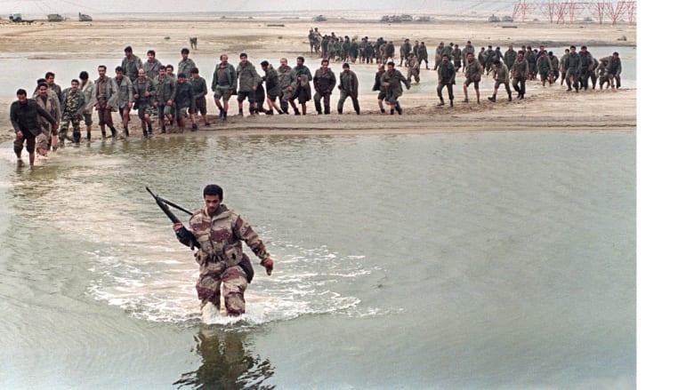 جندي سعودي يقتاد أسرى عراقيين عبر بركة من الماء في صحراء الكويت ، 25 فبراير/ شباط 1991