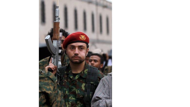 أحد أنصار الحوثي بالزي العسكري، يمضع القات ويرفع السلاح خلال مظاهرة بصنعاء، 26 مارس/ آذار 2015