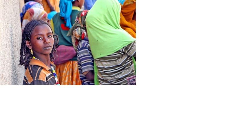 """فتاة من عشيرة """"آرومو"""" بانتظار باعة الحطب المستخدم كوقود"""